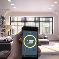 Un personne tient dans sa main un téléphone intelligent dans le salon d'un appartement.
