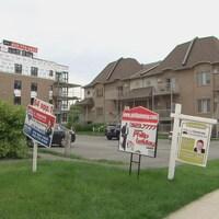 Des pancartes à vendre sur un gazon devant des maisons