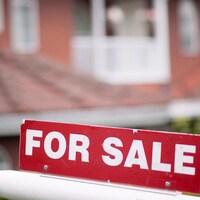 Une affiche en anglais indique qu'une propriété est à vendre.