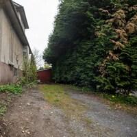 Le petit terrain à vendre est entouré d'une maison et de buissons.