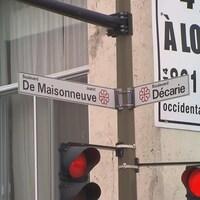 Les pancartes avec les noms des deux boulevards au-dessus du feu de circulation.