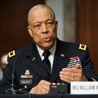Le major-général William Walker, bardé de décorations militaires, s'adresse aux élus, la main devant lui.