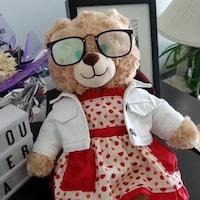 Un ourson en peluche porte des lunettes, une robe avec des coeurs et un blouson. Il est posé sur un meuble.