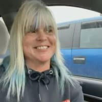 Une femme aux cheveux blonds avec un large sourire est dans sa voiture.