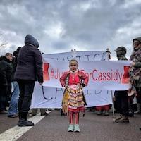 Fillette en vêtements traditionnels micmacs devant une bannière « Justice pour Cassidy » le 21 novembre 2018 à Canso, en Nouvelle-Écosse.
