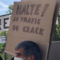 Un homme brandit une pancarte sur laquelle on peut lire : Halte au trafic du crack!