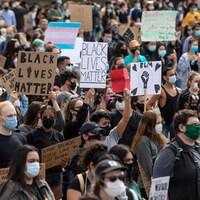 Une foule de manifestants tiennent des pancartes avec des slogans contre le racisme