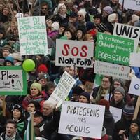 Une foule avec des pancartes.