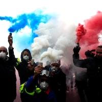 Des ambulanciers qui tiennent des fumigènes bleu, blanc rouge.
