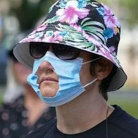 Une femme portant un chapeau, des lunettes de soleil et un masque avec un trou découpé au niveau de la bouche.