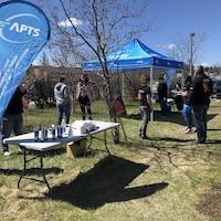 Des membres de l'APTS discutent autour d'une tente aux couleurs du syndicat.