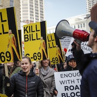 Des manifestants brandissant des pancartes et un homme avec un porte-voix en premier plan