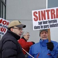Un groupe de manifestants armés de pancartes sont regroupés devant une tour à bureaux.