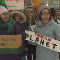 Une poignée de jeunes adolescents scandent un slogan en tenant des panneaux contre la pollution et en faveur de la planète.