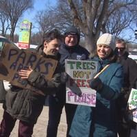 Six personnes, dehors, tenant des pancartes sur lesquelles on peut lire les  slogans : « les parcs sont pour tout le monde », « des arbres, pas des frais ».
