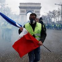 Un manifestant tient un drapeau français sur l'avenue des Champs-Élysées, lors d'une journée nationale de protestation du mouvement des « gilets jaunes » à Paris, le 8 décembre 2018.
