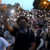 Des manifestants brandissent leur téléphone intelligent lors d'une marche.
