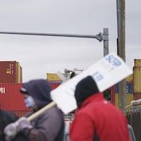 Des débardeurs portant le masque manifestent avec des pancartes du SCFP.