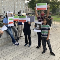 Une dizaine de personnes sont attroupées devant l'Assemblée nationale de Québec et brandissent des pancartes aux couleurs du drapeau iranien, c'est-à-dire vert, blanc et rouge.