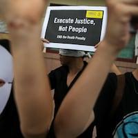 Des manifestants, qui portent des marques de papier, tiennent des pancartes sur lesquelles on peut lire : Execute Justice, not people. (Traduction : Exécutez la justice, pas les gens)