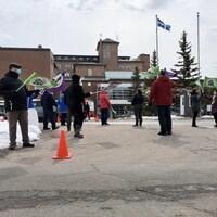 Une manifestation devant l'hôpital de Baie-Comeau. Quelques personnes avec des drapeaux.