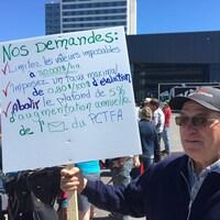 Un homme tient une pancarte énumérant quelques demandes.