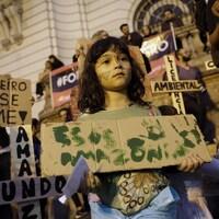 Une enfant porte une pancarte sur laquelle on peut lire «SOS Amazonia» .