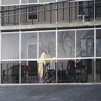 Un travailleur qui porte de l'équipement de protection s'occupe de résidents sur un balcon du Manoir Laurier, à Ottawa.
