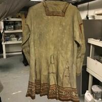 Un manteau en cuir de longueur moyenne, dont le bas est orné de dessins.