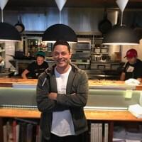 Le restaurateur est au centre de l'image. À l'arrière-plan, des cuisiniers s'affairent devant des appareils de cuisine.