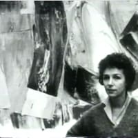 Plan buste de Marcelle Ferron et toile en arrière plan.