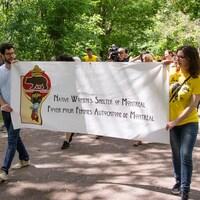 Deux personnes tiennent une bannière avec les mots «Foyer pour femmes autochtones de Montréal» dessus. D'autres personnes les suivent à la marche derrière.