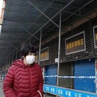 Une femme marche devant le marché de gros des fruits de mer.