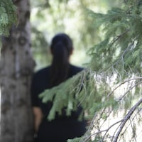 Une fille de dos prend appui sur un arbre dans un parc.