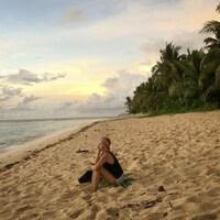 La femme est assise dans le sable fin. Au loin, on voit un coucher de soleil, la mer et des palmiers.