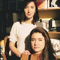 Les deux jeunes femmes, dans un rayon de soleil, regarde la caméra.