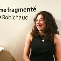Marie-France Robichaud pose à côté de son nom écrit sur le mur d'une galerie.