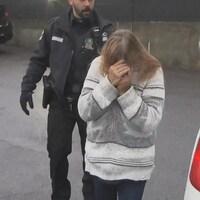Marie-Jeanne Côté, escortée par un policier, se cache le visage avec les mains.