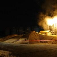 Une flamme s'échappe d'une ferme où une voiture de police est stationnée.