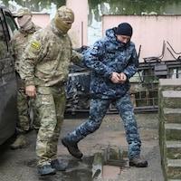 Un policier escorte un soldat menotté.