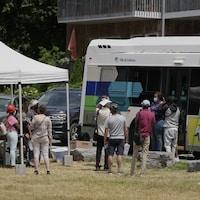 Des gens font la file devant un autobus stationné.
