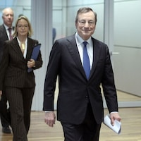 Mario Draghi marche dans un corridor, des feuilles en main.