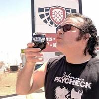 Un homme s'apprête à boire une bière brune de Rebellion Brewing devant les locaux de la brasserie à Regina lors d'une journée ensoleillée.