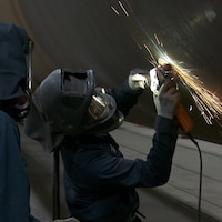 Deux personnes portant des casques travaillent avec un outil qui fait des flamèches.