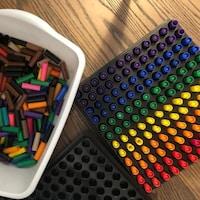 Un jeu créé par Rebecca Saha à partir de bouchons de marqueurs cylindriques rouges, oranges, jaunes, verts, bleus et violets disposés en rangées formant un carré sur un plateau.