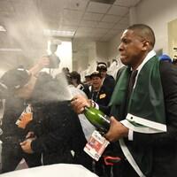 Photo d'un homme qui fait couler une bouteille de champagne dans un vestiaire.