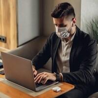 Un homme se sert de son ordinateur portable en portant un masque chirurgical.