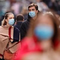 Des passants portant des masques dans la rue.