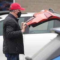Un homme portant un masque referme le coffre de sa voiture dans le stationnement d'un commerce.