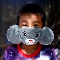 Un jeune garçon, les yeux rieurs, porte un masque qui a l'apparence d'un ours en peluche.